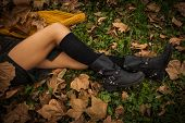 stock photo of woman boots  - woman legs in black leather boots and leggings on grass and autumn leaves - JPG