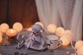 stock photo of wooden horse  - on wooden table lit candle and garland and a wooden horse and bear