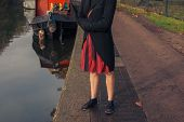 stock photo of houseboats  - A woman is standing by the canal next to a houseboat - JPG