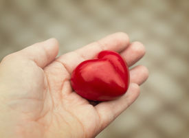 picture of empathy  - Young woman holds out a red heart in her hand concept of love kindness and empathy - JPG