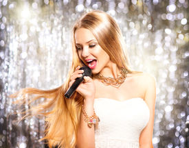 stock photo of karaoke  - Beauty model girl singer with a microphone singing and dancing over holiday glowing background - JPG