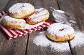 image of donut  - Delicious donuts with icing and powdered sugar on wooden background - JPG