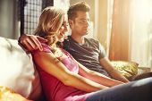 stock photo of futon  - couple watching something at home with lens flare and warm tone to image - JPG