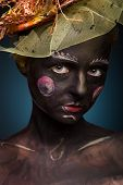 image of black face  - Black painted woman with body art and face art - JPG