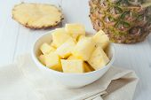 picture of fruit bowl  - pineapple chunks in white bowl on yellow napkin with pineapple pieces at the background - JPG