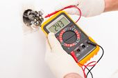 picture of voltage  - Electrician checking socket voltage with digital multimeter - JPG