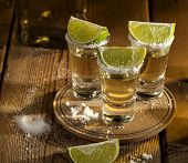 stock photo of lime  - Gold tequila shots with lime fruits on wooden background - JPG
