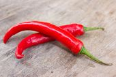 pic of red hot chilli peppers  - Hot red chili or chilli peppers over wooden background - JPG