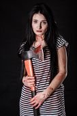 image of bloody  - Young woman with a big bloody axe over black background - JPG