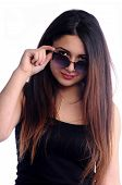 stock photo of valiant  - Pretty girl looking behind glasses and wink - JPG