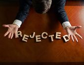 foto of rejection  - Word Rejected made of wooden block letters and devastated middle aged caucasian man in a black suit sitting at the table - JPG