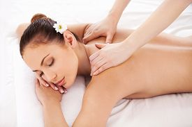 picture of therapist  - Top view of beautiful young woman lying on massage table and keeping eyes closed while massage therapist massaging her shoulders - JPG