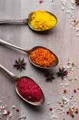 stock photo of saffron  - Different spices selection in old metal spoons over wooden background - JPG