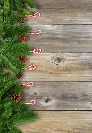 stock photo of candy cane border  - Christmas border with pine tree branches and candy canes on rustic wooden boards - JPG