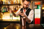 Bartender pouring alcohol beverage in metal glass poster