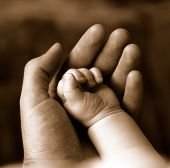stock photo of sleeping baby  - Sepia of father supporting the fist of sleeping baby - JPG