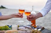Man And Woman Clanging Wine Glasses With Rose Wine At Sunset Beach poster