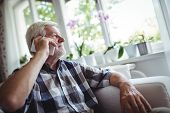 Senior man talking on mobile phone at home poster