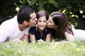 Постер, плакат: Happiness and harmony in family life Happy family concept Young mother and father kissing their da