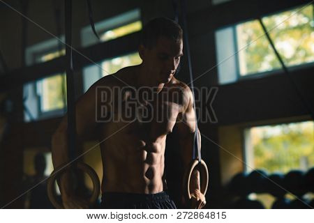 poster of Fit, sporty and athletic sportsman working in a gym. Man training using gymnastic rings. Cross fit,