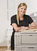 A businesswoman is standing in an office near the copy machine.  She is smiling at the camera.  Vert