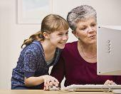 Постер, плакат: Старший женщина и молодая девушка разделяют мышь как они используют компьютер вместе