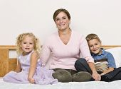 picture of blonde woman  - A mother sits on a bed with her son and daughter as they smile at the camera - JPG