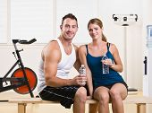Man and woman drinking water in health club