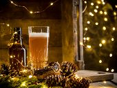 Beer In Glass On Wooden Background With Christmas Lights And Pine Cones poster