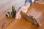 Businessman Hand Stopping Falling Wooden Dominoes Effect From Continuous Toppled Or Risk, Strategy A poster