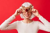 Pretty young girl wearing Christmas deer mask on her face standing isolated over red background poster
