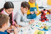 Schoolchildren Making Red Robot With Details And Electric Kit At Desk In Stem Education Class poster