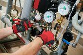 heating engineer or plumber in boiler room installing pipeline manometer poster