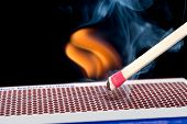 A matchstick lights after it is struck against the striking surface of a match box.