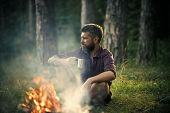 Hipster Hiker With Mug Relax At Bonfire In Forest. Camping, Hiking, Lifestyle. Man Traveler Drink Te poster