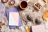 Flat Lay Composition With Notebooks, Cup Of Tea And Wool Balls On Fuzzy Rug poster