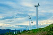 Wind turbines. Wind generators. Wind turbine generators. Alternative energy. Windmills over dramatic poster