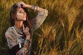 A portrait of a beautiful hippie girl is among a grass. Modern boho style. Beauty, fashion,  poster