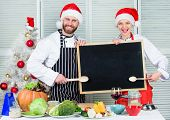 Man And Woman Chef Santa Hat Near Christmas Tree Hold Blackboard Copy Space. Family Traditional Menu poster