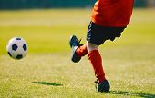 Young Football Player Kicking Ball On The Soccer Pitch. Boy Wearing Red Sports Jersey, Black Shorts, poster