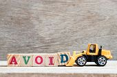 Toy Bulldozer Hold Letter Block D To Complete Word Avoid On Wood Background poster