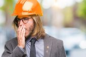 Young handsome architec man with long hair wearing safety helmet over isolated background bored yawn poster