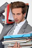 stock photo of workhorses  - Man overwhelmed by files - JPG