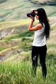 Young brown haired woman photographing in Tuscany