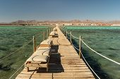 Pier With Chaise Longues In The Red Sea In Resort. Summer Vacation On Red Sea. View At A Clear Sea W poster