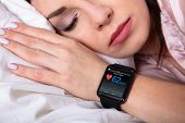 Beautiful Woman Sleeping On Bed With Smartwatch Showing Heartbeat Rate poster