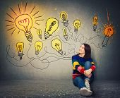 Young Woman Sitting On The Floor Smiling Looking At Bright Lightbulbs On The Wall. Smart And Ingenio poster