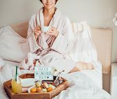 Good Morning Concept. Croped Woman In Bathrobe Sitting On The Bed, Drinking Coffee And Has Her Break poster