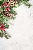 Christmas Flatlay Background With Fir Tree Brunch And Red Decorations On White Stone Background. Top poster