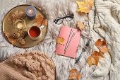 Flat Lay Composition With Book, Cup Of Tea And Warm Clothes On Fuzzy Rug poster